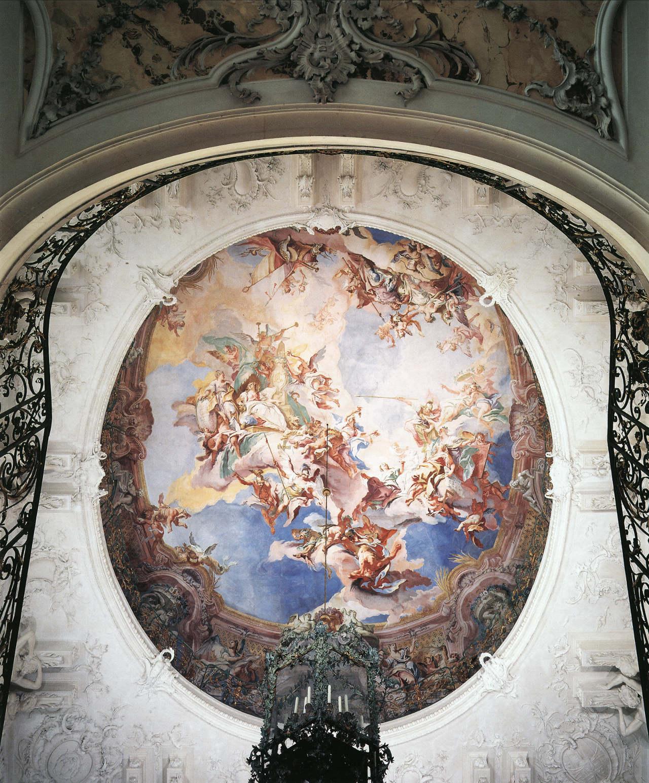 """um 1750, Deckengemälde Treppenhaus Schloß Augustusburg Brühl.<br> Quelle: <a href=""""http://prometheus.uni-koeln.de/pandora/image/show/heidicon_kg-649ef52164245e156c43c14d901bea8696c225b9"""">Prometheus</a>; publiziert in Merten, Klaus: Burgen und Schlösser in Deutschland. München 1995: Hirmer, 288.<br>  Lizenz: Zitat eines urheberrechtlich geschützten Werks (§ 51 UrhG) <br> <strong>Erläuterung:</strong> Die Darstellung hat die Protektion der Künste durch fürstliche Großmut zum Thema. Die Verbindung vom Schutz der Künste mit der Verherrlichung des Hausherrn, Kurfürst Clemens August, wird über die Figur der Magnanimitas hergestellt, verläuft somit über die Allegorie. Abgeleitet vom kurfürstlichen Wahlspruch """"Pietate et Magnanimitate"""" werden die Künste, die sich mit ihren Attributen auf einer Wolke am rechten Bildrand versammelt haben, zur thronenden fürstlichen Großmut geleitet. Minerva weist ihnen den Weg hinauf zu dem von Magnifizenz und Freigebigkeit umgebenen fürstlichen Thron. Das kurfürstliche Wappentier und die Kartusche mit Monogramm am Obelisken verdeutlichen die allegorische Lesart als Glorifizierung Clemens Augusts. Das Programm des Kunsthelden enthält ebenso eine kämpferische Komponente, ebenfalls durch Personifikationen verhandelt: Merkur und Virtus stürzen Invidia und Luxuria in die Tiefe."""