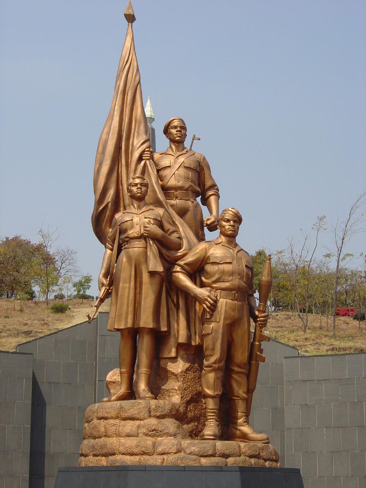 "Grab des Unbekannten Soldaten. Die Bronzestatue zeigt drei bewaffnete Guerillakämpfer – zwei Männer, eine Frau.<br> Quelle: <a href=""https://commons.wikimedia.org/wiki/File:Heroes_Acre_Monument,_Harare,_Zimbabwe.jpg"">Gary Bembridge / Wikimedia Commons</a><br> Lizenz: <a href=""https://creativecommons.org/licenses/by/2.0/de/"">Creative Commons BY 2.0</a>"
