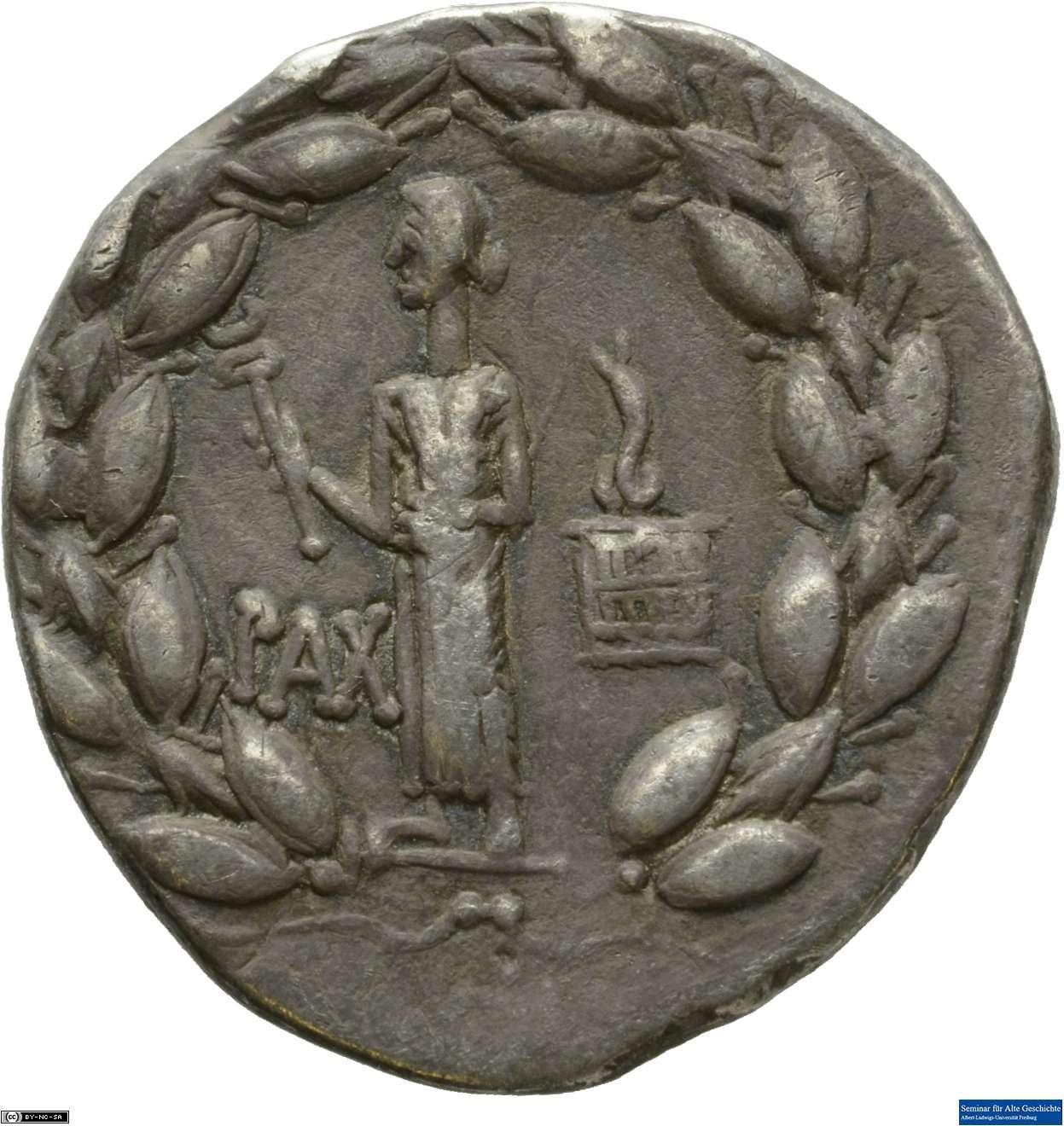 """Pax aufrecht stehend und nach links gewandt hält einen <em>caduceus</em> in der Rechten und steht auf einem Schwert; im rechten Bildfeld eine <em>cista mystica</em> mit emporstrebender Schlange; eingefasst in einen Lorbeerkranz. Cistophor aus Ephesos, 28 v. Chr., Silber, Durchmesser 2,8 cm, Gewicht 11,49 g, Freiburg, Seminar für Alte Geschichte (aktuell im Uniseum MU-001/25), Inv.-Nr. 00535. <br>Quelle: Münzsammlung des Seminars für Alte Geschichte, Universität Freiburg<br>Lizenz: <a href=""""https://creativecommons.org/licenses/by-nc-sa/3.0/de/"""">Creative Commons BY-NC-SA 3.0</a>"""