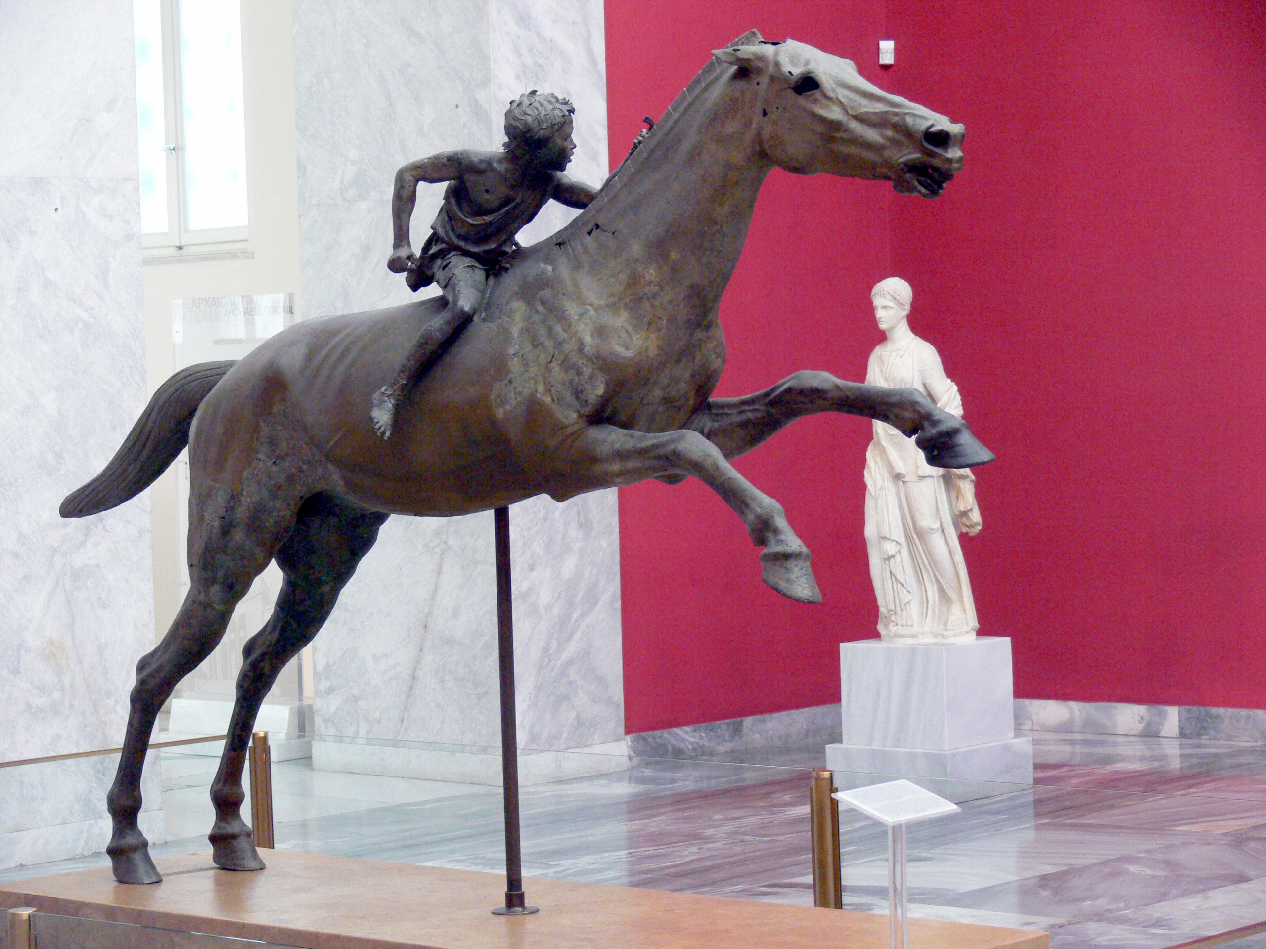 "ca. 150–140 v. Chr., Bronze, 290 cm x 210 cm, Athen, Archäologisches Nationalmuseum, Inv.-Nr. X 15177.<br>Quelle: <a href=""https://commons.wikimedia.org/wiki/File:07Jockey01.jpg"">User:Fingalo / Wikimedia Commons</a>