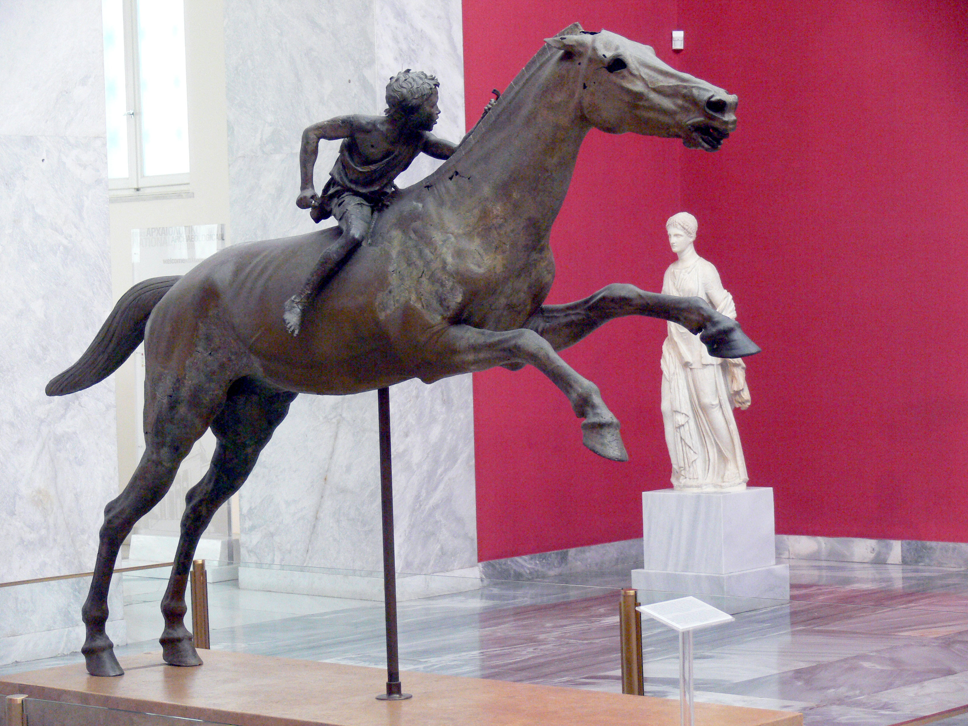 "ca. 150–140 v. Chr., Bronze, 290 cm x 210 cm, Athen, Archäologisches Nationalmuseum, Inv.-Nr. X 15177.<br>Quelle: <a href=""https://commons.wikimedia.org/wiki/File:07Jockey01.jpg