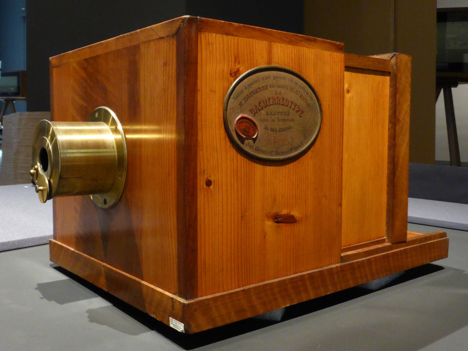 """Die erste Kamera, die in größerer Stückzahl zum Kauf angeboten wurde, war die <em>Giroux Daguerréotype</em>. Diese Schiebekastenkamera aus dem Jahr 1839 funktionierte nach dem Daguerreotypie-Verfahren. An der Seite kennzeichnet sie eine Plakette mit dem Siegel von Alphonse Giroux und Louis Daguerres Unterschrift als Original.<br> Quelle: <a href=""""https://commons.wikimedia.org/wiki/File:C%C3%A1mara_para_obtener_vistas_al_daguerrotipo,_original_del_a%C3%B1o_1839,_conservada_en_Barcelona,_Espa%C3%B1a,_Spain.jpg"""">User:CARLOS TEIXIDOR CADENAS / Wikimedia Commons</a><br> Lizenz: <a href=""""https://creativecommons.org/licenses/by-sa/4.0/deed.de"""">Creative Commons BY-SA 4.0</a>"""
