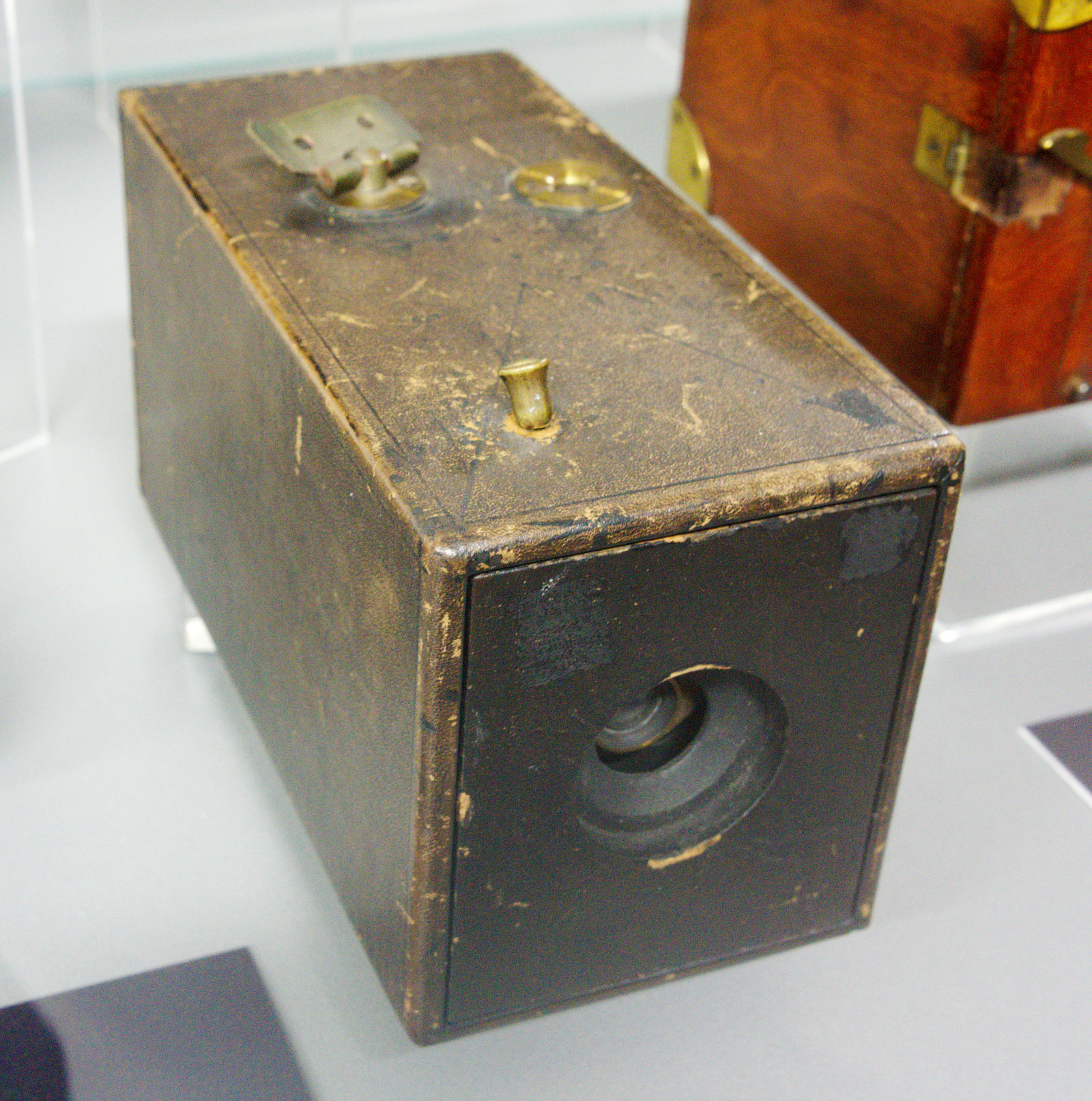 """Die <em>Kodak Nr. 1</em>, hergestellt zwischen 1889 und 1895, ist die bekannteste unter den vielen Handkameras, die im letzten Drittel des 19. Jahrhunderts produziert wurden und die Verbreitung der Amateurfotografie beschleunigten. Ihre Berühmtheit verdankt sie maßgeblich den Angaben der Firma Kodak, die den Eindruck erwecken, als habe die Kodak Nr. 1 die Amateur- und Rollfilmfotografie begründet. Neuere Forschungen haben diese Deutung, die seither vielfach unkritisch reproduziert wurde, jedoch infrage gestellt. (Vgl. Starl, Timm: Knipser. Die Bildgeschichte der privaten Fotografie in Deutschland und Österreich von 1880 bis 1980. München 1995: Koehler & Amelang, 45-50.)<br> Quelle: <a href=""""https://commons.wikimedia.org/wiki/File:Kodak_nr_1.jpg"""">User:Bronger / Wikimedia Commons</a><br> Lizenz: <a href=""""https://creativecommons.org/publicdomain/zero/1.0/deed.de"""">Public Domain / CC0 1.0</a>"""