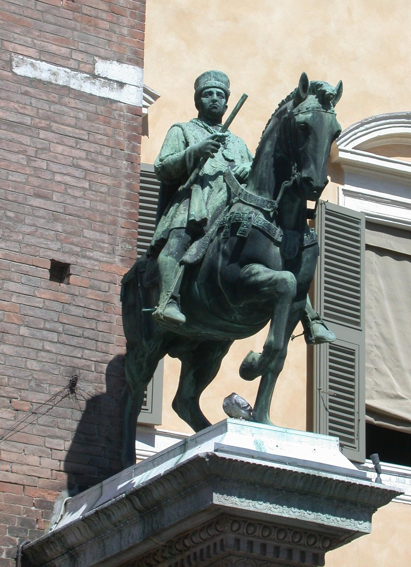 """vor dem Palazzo Communale in Ferrara. Kopie nach der Statue von 1451 durch Giacomo Zilocchi (1927).<br> Quelle: Riccardo Speziari, <a href=""""https://commons.wikimedia.org/wiki/File:Ferrara_-_Statua_di_Niccolo_III_d%27Este_2.jpg"""">Wikimedia Commons / User:RicciSpeziari</a><br> Lizenz: <a href=""""https://creativecommons.org/licenses/by-sa/3.0/deed.de"""">Creative Commons BY-SA 3.0</a>"""