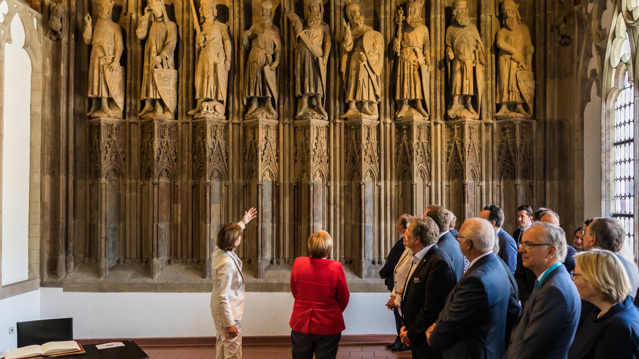 "Abb. 16: Bundeskanzlerin Angela Merkel besichtigt die ""Neun Guten Helden"""